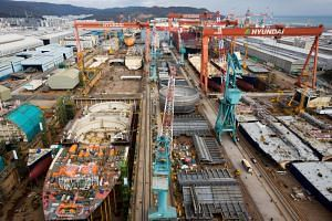 Ships stand under construction in the dry dock at the Hyundai Heavy Industries Co shipyard in Ulsan, South Korea.