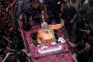 India's Prime Minister Narendra Modi waving at supporters during a roadshow in Varanasi on Thursday. He has so far chosen to represent Varanasi in Parliament and is not likely to pursue any other seat in the country's 39-day staggered general electio