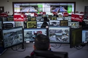 A control room of Ecuador's emergency response system. Police at 16 monitoring centres spend their days poring over footage from 4,300 high-powered cameras across the country. Armed with joysticks, they control the cameras and scan the streets for dr