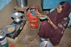 Madam Reena Devi cleaning a gas cylinder as she prepares food on a stove in Nisarpura village on the outskirts of Patna.