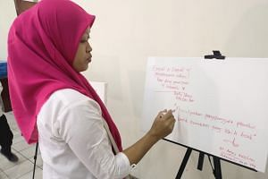 Ms Masnun, 38, a widow of a security official assigned to a Bekasi polling station who died of exhaustion, points to a white board containing praises on her late husband and other victims.