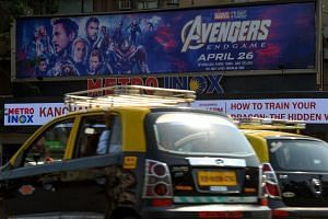 Indian vehicles go past a movie theatre displaying a poster of the latest Avengers movie, in Mumbai, on April 25, 2019.
