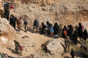 ISIS fighters and their families walk as they surrendered in the village of Baghouz, Syria, on March 12, 2019.