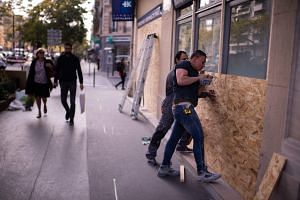 Workers put wood panels in place to protect a shop in Paris on April 30, 2019, ahead of expected demonstrations and rallies to mark May Day.