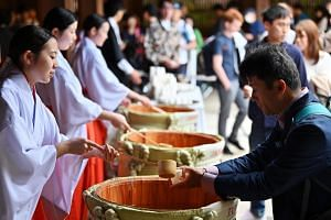 People receive Japanese sake to celebrate the change of an era at Meiji Shrine in Tokyo on May 1, 2019.