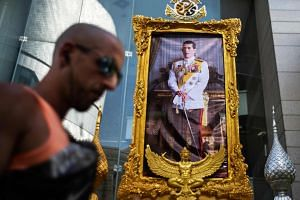 A tourist walks past a portrait of Thailand's King Maha Vajiralongkorn in Bangkok, on May 1, 2019, ahead of his coronation that will take place from May 4 to 6.