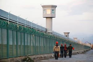 Workers walk by the perimeter fence of what is officially known as a vocational skills education centre in Xinjiang, China, on Sept 4, 2018.
