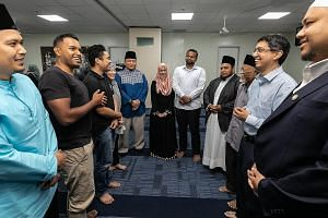 Senior Parliamentary Secretary for Social and Family Development and Education Muhammad Faishal Ibrahim (second from right) talking to wedding solemnisers and couples during the announcement of the Bersamamu programme yesterday at the Al-Mukminin Mos