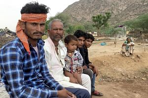 Mr Baghrawat Panwar (far left), 30, a member of the Banjara community now settled near the foothills of the ancient Aravalli range. The settlement is shorn of any public utilities. None of the residents has been given ownership of the land they are s