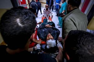 Paramedics push a stretcher carrying the body of a wounded Palestinian at a hospital in Beit Lahia, northern Gaza strip on May 5, 2019.