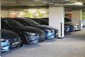 Unused private-hire cars at the Singapore Sports Hub last month. Industry estimates put the fleet of unused vehicles - mostly left behind by Uber - at over 2,000. Yet, to entice drivers, the private-hire sector has placed orders for hundreds of BMW,