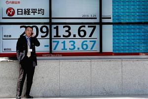 A man stands in front of an electronic board showing the Nikkei stock index outside a brokerage in Tokyo, Japan.