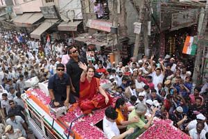 Wearing a dark red sari, Mrs Priyanka Gandhi Vadra is showered with rose petals as her bus makes its way through New Delhi, on May 8. Her presence in these elections is seen as an attempt to bulk up the Congress party's campaign.