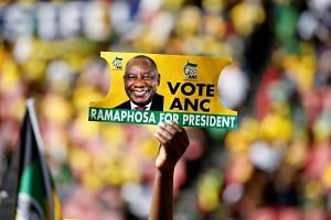 A supporter holds a placard with the face of African National Congress' Cyril Ramaphosa, during a rally in Johannesburg, South Africa, on May 5, 2019.