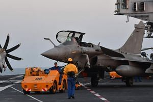 French servicemen and crew line up Rafale fighter jets for take off from the aircraft carrier Charles de Gaulle during a joint Indo-French naval exercise Varuna, in the Arabian sea, off Goa coast on May 9, 2019.