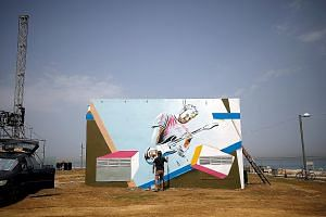 A man painting a mural on a structure near the Eurovision Village, a space for fans of the song contest to be held in Tel Aviv next week. Israel's Prime Minister Benjamin Netanyahu's ceasefire deal with Hamas is partly seen as ensuring the Eurovision