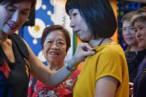Minister for Manpower and Second Minister for Home Affairs Josephine Teo putting a collar pin onto the blouse of homemaker Jenny Sim during the Everyday (Her)oes initiative at the HomeTeamNS clubhouse in Our Tampines Hub on May 12, 2019.