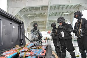 Boarding teams from Brunei, India, South Korea and Singapore conducting security checks on a simulated vessel of interest.
