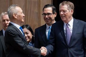 Chinese Vice Premier Liu He (left) shakes hands with US Trade Representative Robert Lighthizer (right) alongside US Treasury Secretary Steven Mnuchin as Liu leaves the Office of the United States Trade Representative after trade negotiations in Washi