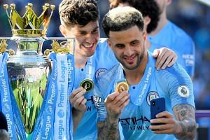 Manchester City's Kyle Walker and John Stones pose for a photo with their medals during the presentation after the match.