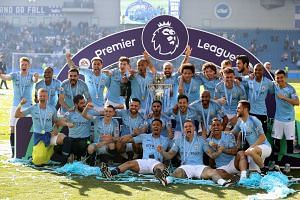 Manchester City players and staff celebrate with the Premier League trophy after the English Premier League soccer match between Brighton & Hove Albion and Manchester City at the AMEX Stadium.