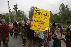 Female Kashmiri Muslim protesters shout slogans and carry placards during a protest on the outskirts of Srinagar, the summer capital of Indian Kashmir, on May 13, 2019.