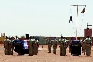 French soldiers of the counter-terrorism Barkhane mission in Africa's Sahel region standing guard by the coffins of their comrades during a funeral cerenomy at their base camp in northern Burkina Faso, on May 13, 2019.