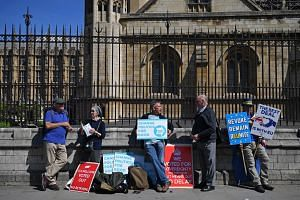 Pro-Brexit and anti-Brexit activists stand in the afternoon sunshine with their placards outside the Palace of Westminster in central London on May 13, 2019.