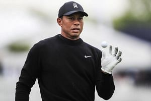 Tiger Woods catches a ball tossed to him on the driving range during practice for the 2019 PGA Championship at Bethpage Black in Farmingdale, New York, on May 14, 2019.
