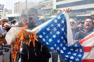 Demonstrators burn a US flag to show their support of Iran's decision to pull out from some part of the nuclear deal in Teheran on May 10, 2019.