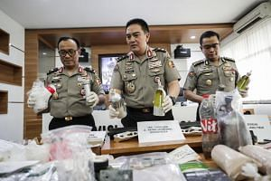 Indonesian national police spokesman Muhammad Iqbal (centre) shows the evidence seized in the arrest of suspected militants during a press conference at the police headquarters in Jakarta, Indonesia, on May 17, 2019.