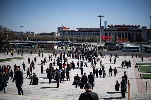"""Officials and pedestrians outside the Great Hall of the People in Beijing, on March 12, 2019. The Communist Party's People's Daily described China's determination to protect its national interests and dignity as being as """"firm as a boulder""""."""