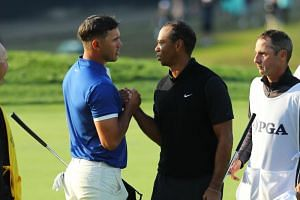 Brooks Koepka and Tiger Woods shake hands on the 18th green during the second round of the 2019 PGA Championship at the Bethpage Black course in in Farmingdale, New York, on May 17, 2019.