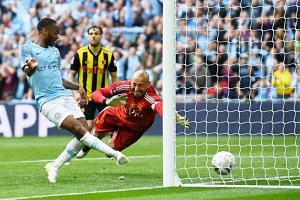 Raheem Sterling (left) of Manchester City scores the 6-0 during the English FA Cup final between Manchester City and Watford at Wembley Stadium in London, on May 18, 2019.
