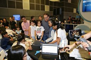 Minister for Communications and Information S. Iswaran looking at the work of CHIJ Toa Payoh pupils who did coding utilising artificial intelligence to benefit people with disabilities at the SG:Digital Wonderland 2019.