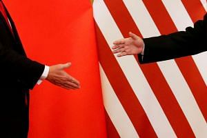 US President Donald Trump and China's President Xi Jinping reaching out to shake hands in 2017 at the Great Hall of the People in Beijing. There is nothing inevitable about the rise of China, the decline of the US, or an eventual clash between the