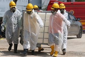 Emergency personnel wearing protective suits preparing materials for the clean up of Sungai Kim Kim river in Pasir Gudang, on March 14, 2019.