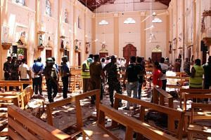 Sri Lankan security personnel walk through debris following the explosion in St Sebastian's Church in Negombo, north of Colombo, on April 21, 2019.
