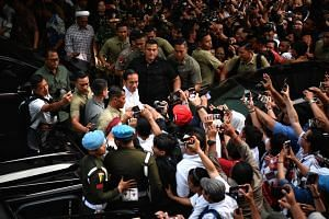 Supporters loudly cheer at incumbent president Joko Widodo as he leaves Djakarta Theatre in Jakarta where he met leaders of political parties supporting his ticket. President Jokowi, as he is popularly known, was re-elected, winning 55.5 per cent of