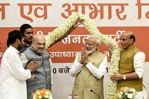 Bharatiya Janata Party president Amit Shah (left) and Indian Prime Minister Narendra Modi garlanded during a ceremony to thank the Union Council of Ministers for their contribution in India's general election.