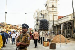 A Sri Lankan policeman stands guard as Catholic devotees take part in a remembrance ceremony in front of St Anthony's Church in Colombo on May 21, 2019.