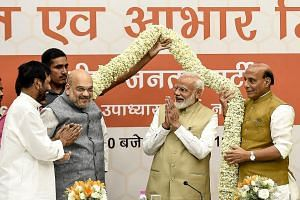 Bharatiya Janata Party (BJP) president Amit Shah (third from left) and Indian Prime Minister Narendra Modi (second from right) receiving a garland at a meeting in the BJP's New Delhi headquarters on Tuesday.