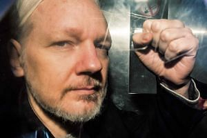 WikiLeaks founder Julian Assange gestures from the window of a prison van as he is driven into Southwark Crown Court in London, on May 1, 2019.
