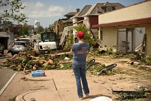 "A resident taking photos of debris following a tornado in Jefferson City in the US state of Missouri. Officials said a ""massive"" twister on Wednesday caused widespread damage in the state capital but no fatalities. However, three deaths and several i"