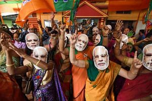 Supporters of the Bharatiya Janata Party (BJP), some wearing masks of Indian Prime Minister Narendra Modi, celebrating the decisive mandate won by their party on Thursday at the BJP office in Guwahati.