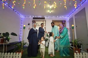 (From left) Ms Siti Juliana Saptu, her husband Mr Muhammad Sabri Johari and their children, with their next-door neighbours Mr Shaieful Azan Zanal Abidin and his wife Ms Siti Zulaifa Sukardi, stand in the corridor they decorated together for Hari Ray