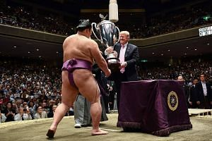 United States President Donald Trump presenting Sumo tournament winner Asanoyama with a custom-made trophy called the US President's Cup.