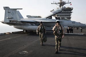 "A US Navy pilot and a weapons system officer from the VFA-11 ""Red Rippers"" squadron after returning to the aircraft carrier USS Theodore Roosevelt in the Persian Gulf on Aug 6, 2015. The squadron began noticing strange objects just after the Navy"