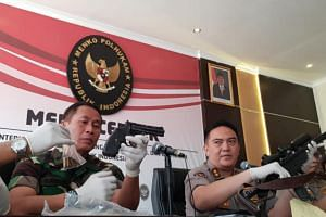 National police spokesman Mohammad Iqbal (right) and army officials show firearms and bullets confiscated from new suspects in last week's riots in Jakarta to reporters on May 27, 2019.