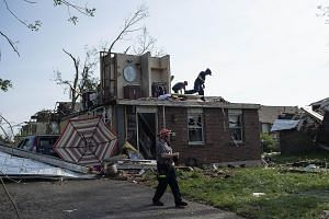 Firefighters and rescue crews searching houses for people trapped or injured following powerful storms yesterday in the US state of Ohio. PHOTO: AGENCE FRANCE-PRESSE